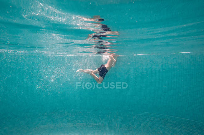 Boy in trunks swimming in transparent turquoise deep pool — Stock Photo