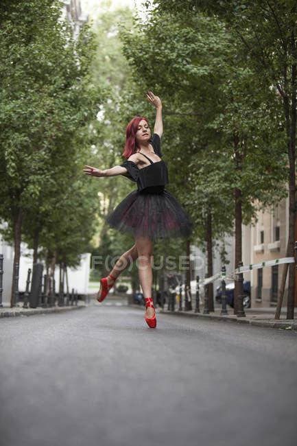 Ballerine à tête rouge avec tutu noir et pointes de ballet rouge dansant dans la rue avec des arbres en arrière-plan . — Photo de stock