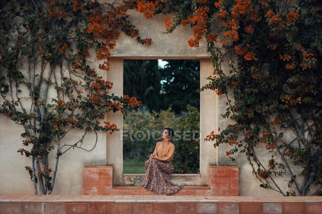 Bella donna afro-americana in estate panni leggeri seduti su un gradino di pietra nel parco e guardando altrove — Foto stock