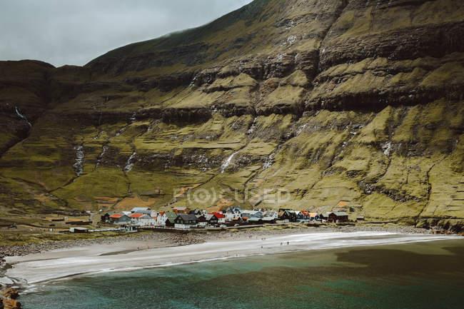 Pequena aldeia pitoresca costa verde encosta nas Ilhas Feroe — Fotografia de Stock
