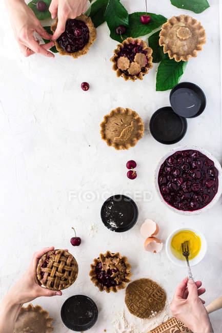 Руки человека, подготовке Тарталетки с ягодной начинкой на белом фоне — стоковое фото
