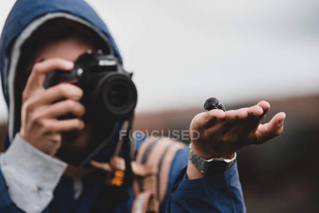 Jovem de casaco quente com capuz segurando lesma preta na palma da mão e tirando foto com câmera de foto no fundo embaçado — Fotografia de Stock