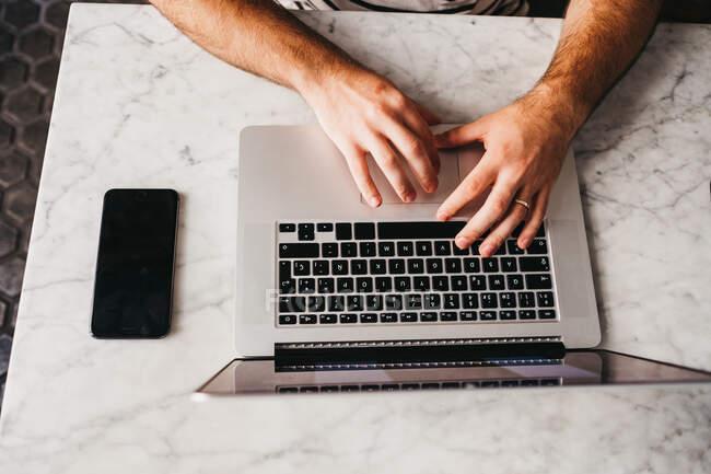 Recorte disparado desde arriba del hombre usando el ordenador portátil sentado en la mesa de mármol con el teléfono cerca - foto de stock
