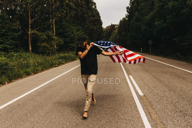 Человек с флагом США бежит по дороге — стоковое фото