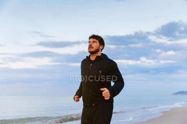 Уверенный в себе бородатый человек в спортивной одежде бежит по песку на море на закате — стоковое фото