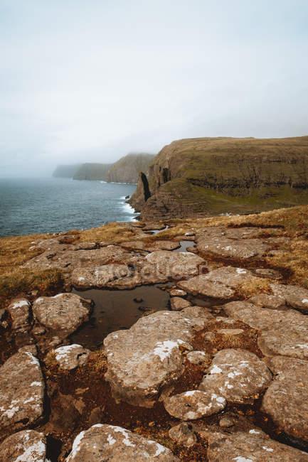 Oceano e maestose scogliere rocciose sulle isole Feroe — Foto stock