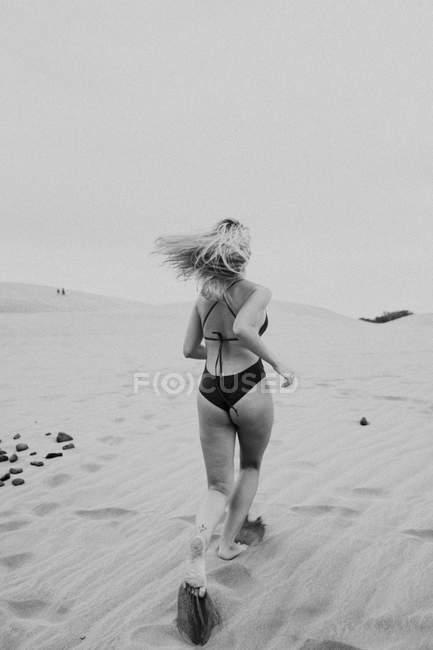 Анонимная блондинка в купальниках бегает по песку — стоковое фото