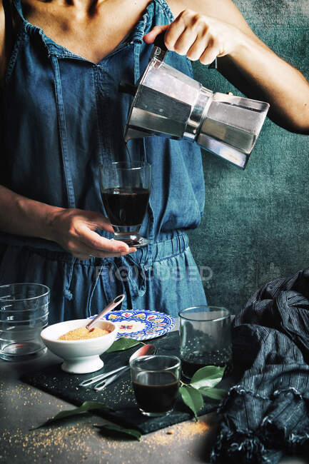 Woman serving coffee in crystal glass — Stock Photo