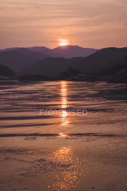 Pittoresco tramonto sul fiume e la silhouette delle montagne sullo sfondo — Foto stock
