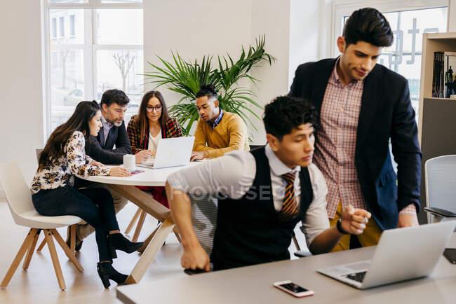 Hommes et femmes multiraciaux assis et debout sur des ordinateurs portables tout en travaillant ensemble. — Photo de stock