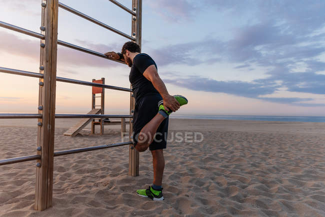 Muscular guy in sportswear doing warming up exercise for legs while standing near ladder during sunset on beach — Stock Photo