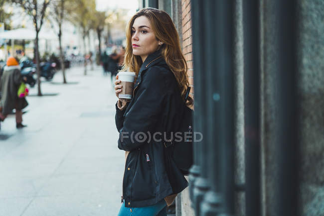 Молодая женщина с бумажной чашкой кофе стоит на улице — стоковое фото
