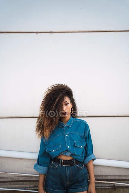 Giovane donna in denim vestiti in piedi sul balcone vicino ringhiera — Foto stock