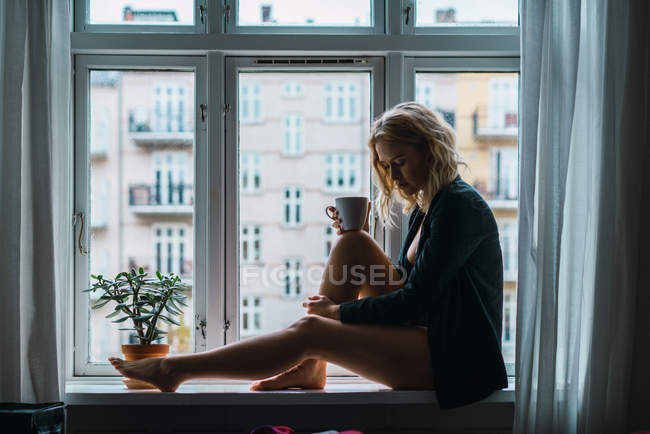 Романтический блондинка молодой женщины, сидя на подоконнике с кофе — стоковое фото