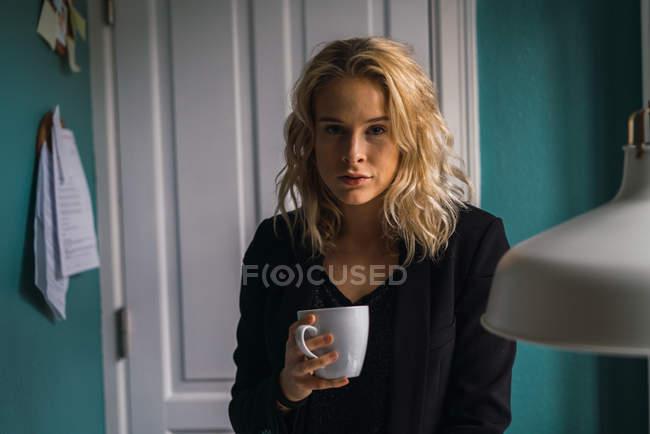 Портрет блондинка молода жінка, стоячи з чашкою кави в домашніх умовах — стокове фото
