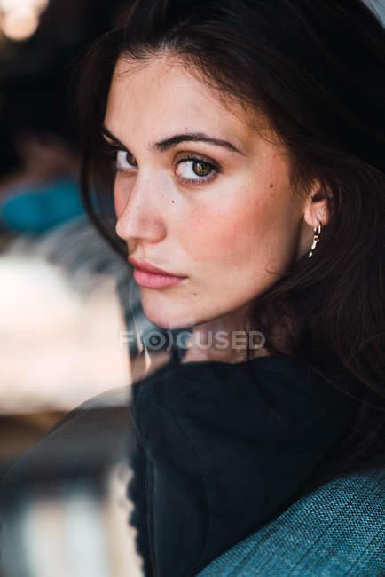 Молодая чувственная брюнетка сидит в кресле и смотрит в камеру — стоковое фото