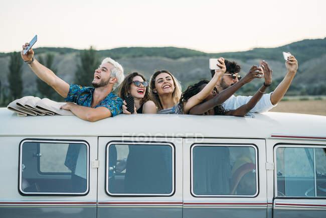 Група радісних різних людей стоїть всередині вінтажного фургона з відкритим дахом і позує за селфі під час подорожі в сільській місцевості разом — стокове фото