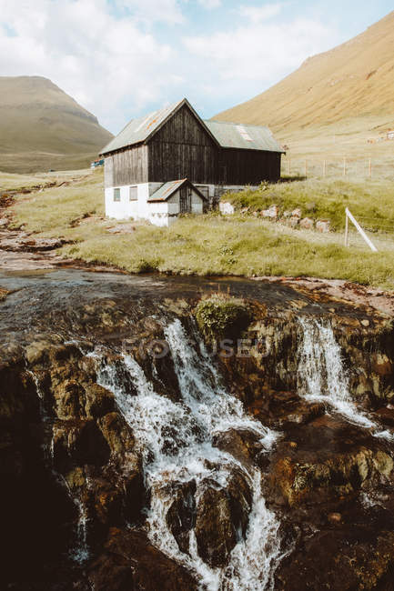 Cascade et maison rurale en bois à flanc de colline sur les îles Feroe — Photo de stock