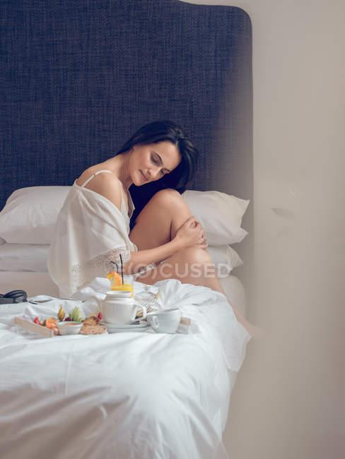 Junge Frau frühstückt sitzend im Bett — Stockfoto