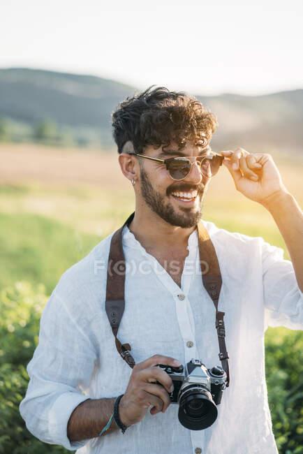 Bonito cara jovem em óculos de sol alegremente sorrindo e segurando câmera de foto retro enquanto está de pé no fundo borrado do campo incrível — Fotografia de Stock