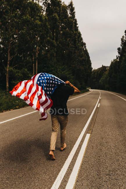 Visão traseira do homem descalço segurando bandeira dos EUA e correndo ao longo da estrada rural estreita — Fotografia de Stock