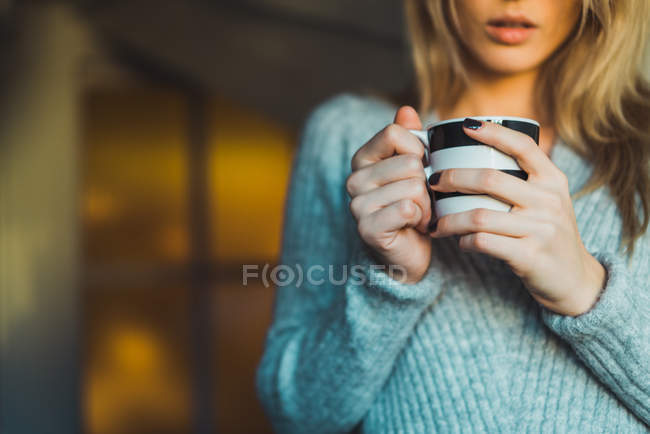 Close-up of woman in grey sweater holding cup of drink — Stock Photo