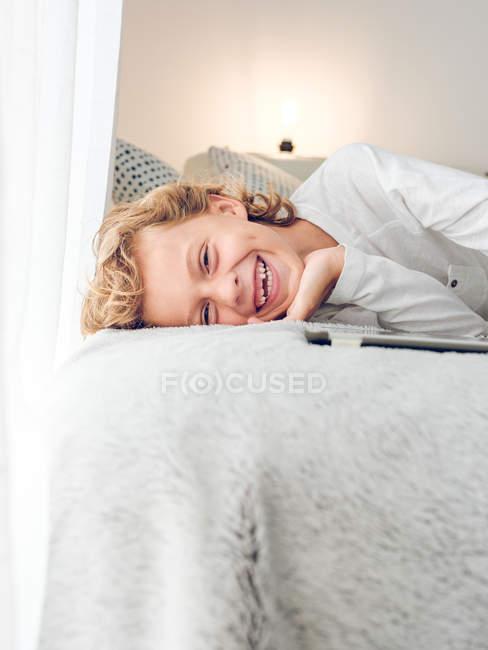 Netter lachender Junge liegt mit digitalem Tablet auf Sofa — Stockfoto