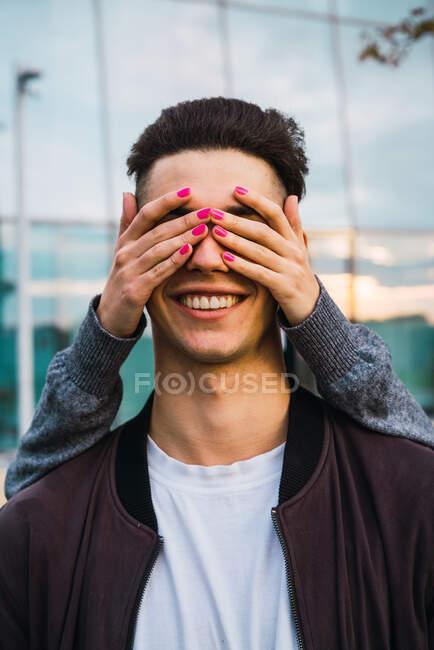 Анонімна жінка закриває очі усміхаючому хлопцю. — стокове фото