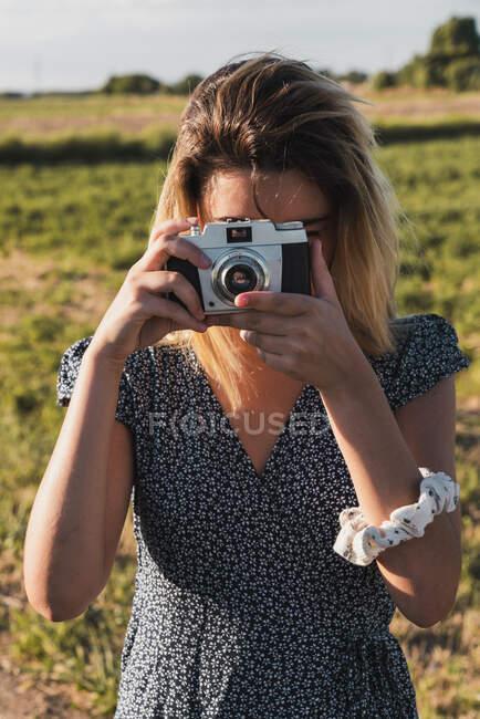 Женщина в платье фотографируется с ретро-камерой на фоне зеленого летнего пейзажа в солнечном свете — стоковое фото