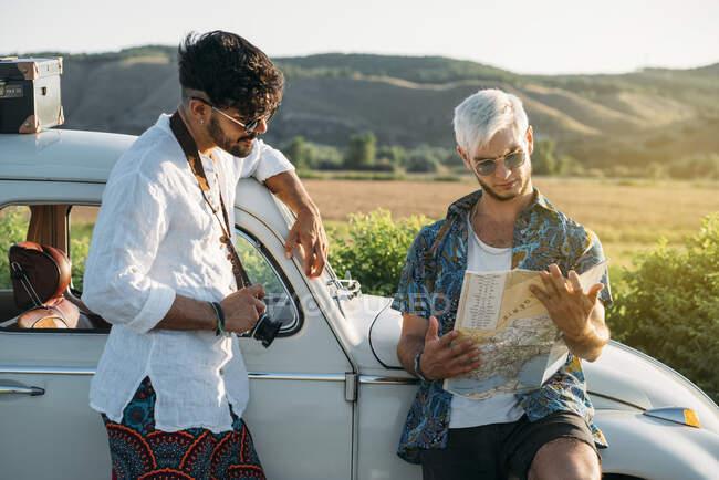 Два молодых парня с фотоаппаратом стоят возле ретро-машины и смотрят на карту, путешествуя вместе на природе — стоковое фото