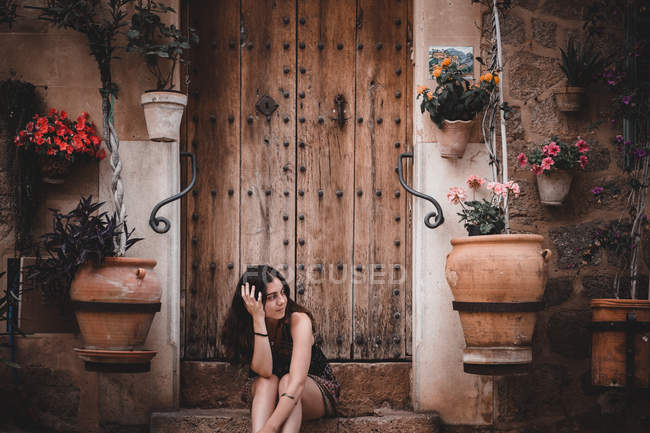 Woman looking away while sitting on doorstep of ancient building decorated with potted flowers in Mallorca, Spain — Stock Photo