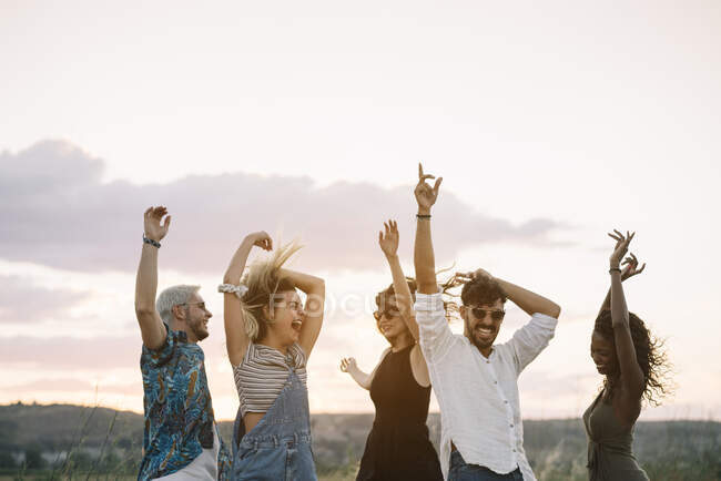 Group of young people in casual outfits laughing and dancing while having fun in beautiful countryside together — Stock Photo