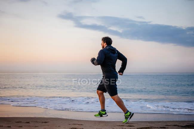 Человек в спортивной одежде бегает по песку в море во время тренировки на пляже на закате — стоковое фото