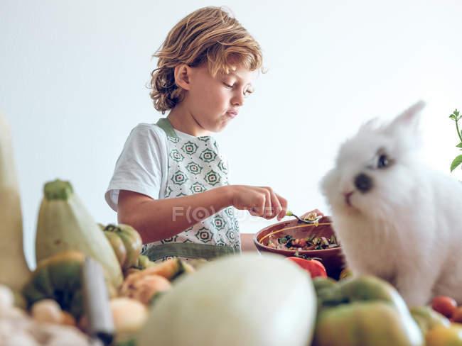 Молодой мальчик стоит и готовит овощи за столом с очаровательным белым кроликом — стоковое фото