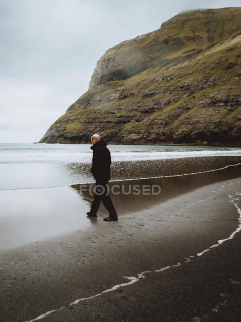 Homem em roupas quentes em pé na costa do oceano calmo em Feroe Island — Fotografia de Stock