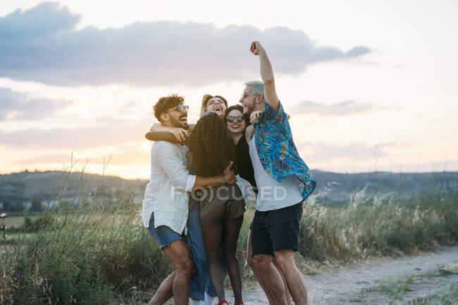Группа молодых людей в повседневной одежде смеются и танцуют, веселясь в красивой сельской местности вместе — стоковое фото