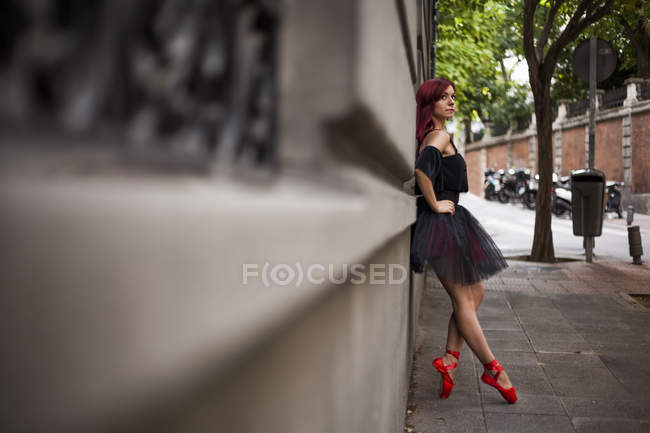 Рыжая балерина с черной пачкой и красными балетными кончиками, разогревающаяся, чтобы танцевать на улице, исполняющая позы, напечатанная на стене — стоковое фото