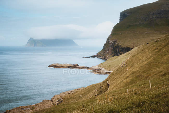 Oceano e falésia rochosa em nublado nas Ilhas Feroe — Fotografia de Stock