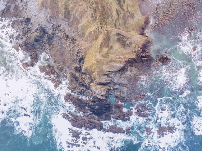 Incredibile vista di acqua di mare spruzzi vicino a una lunga scogliera rocciosa nella giornata nuvolosa nelle Asturie, Spagna — Foto stock