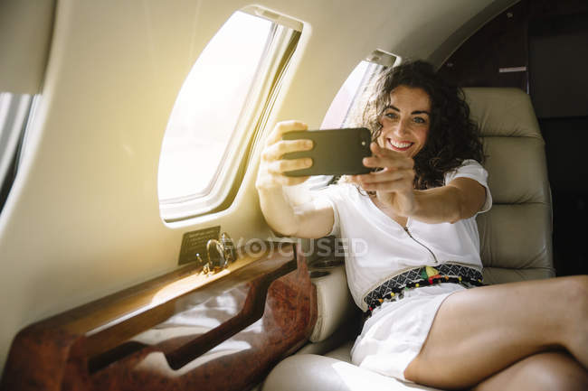 Femme joyeuse prendre selfie en avion — Photo de stock