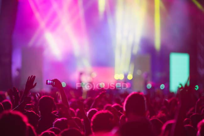 Anonyme Menschen, die Hände in die Höhe halten und jubeln, während sie Zeit mit erstaunlicher Musikshow verbringen — Stockfoto