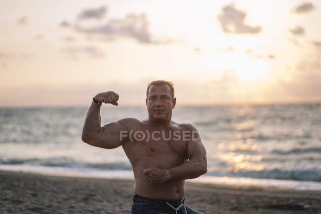 Viejo fuerte hace ejercicio en la playa - foto de stock
