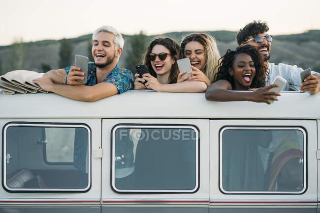 Друзья, использующие смартфоны в фургоне — стоковое фото