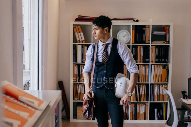 Пристойний молодий азіат, що стоїть в офісі й озирається.. — стокове фото