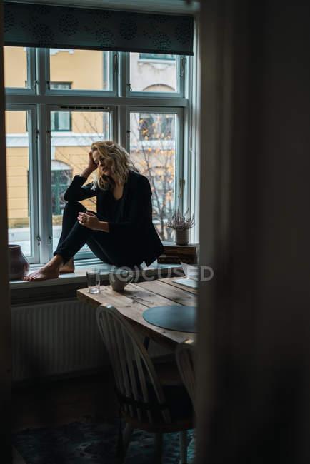 Romantica bionda giovane donna seduta sul davanzale della finestra — Foto stock