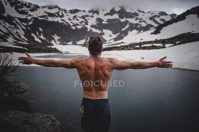 Vue arrière de l'homme musclé aux bras tendus dans la nature enneigée — Photo de stock
