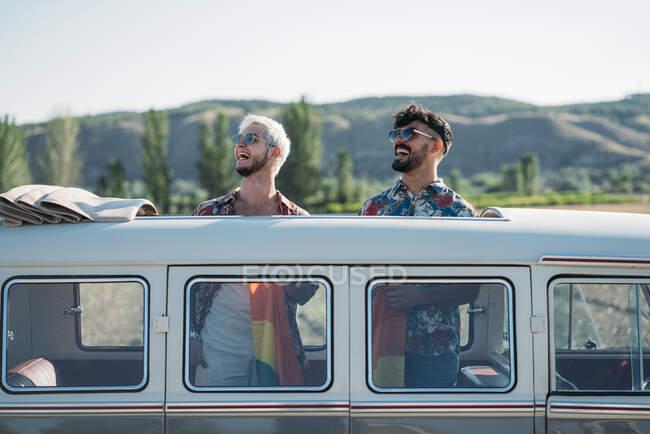 Двое молодых людей, обнимающих и держащих ЛГБТ-флаг над головами, стоя внутри фургона с открытой крышей в природе — стоковое фото