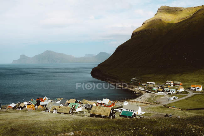 Vista da pequena aldeia com casas coloridas e verdes montanhas em Ilhas Feroe — Fotografia de Stock