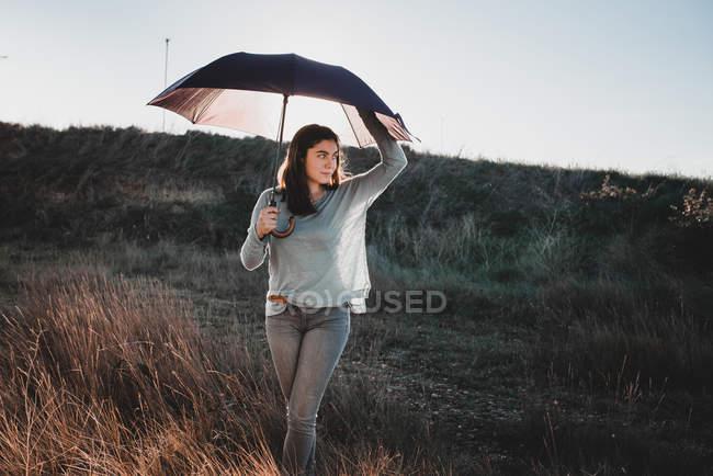 Attrayant jeune femme tenant un parapluie et regardant loin tout en se tenant dans une magnifique prairie en Navarre, Espagne — Photo de stock