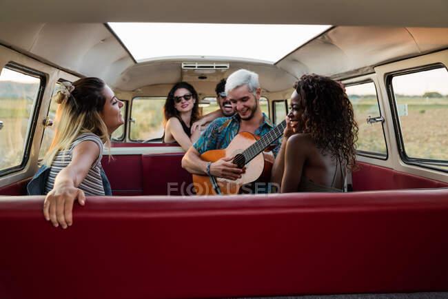 Группа молодых людей смеется и слушает красивого парня, играющего на акустической гитаре в винтажном фургоне на природе — стоковое фото
